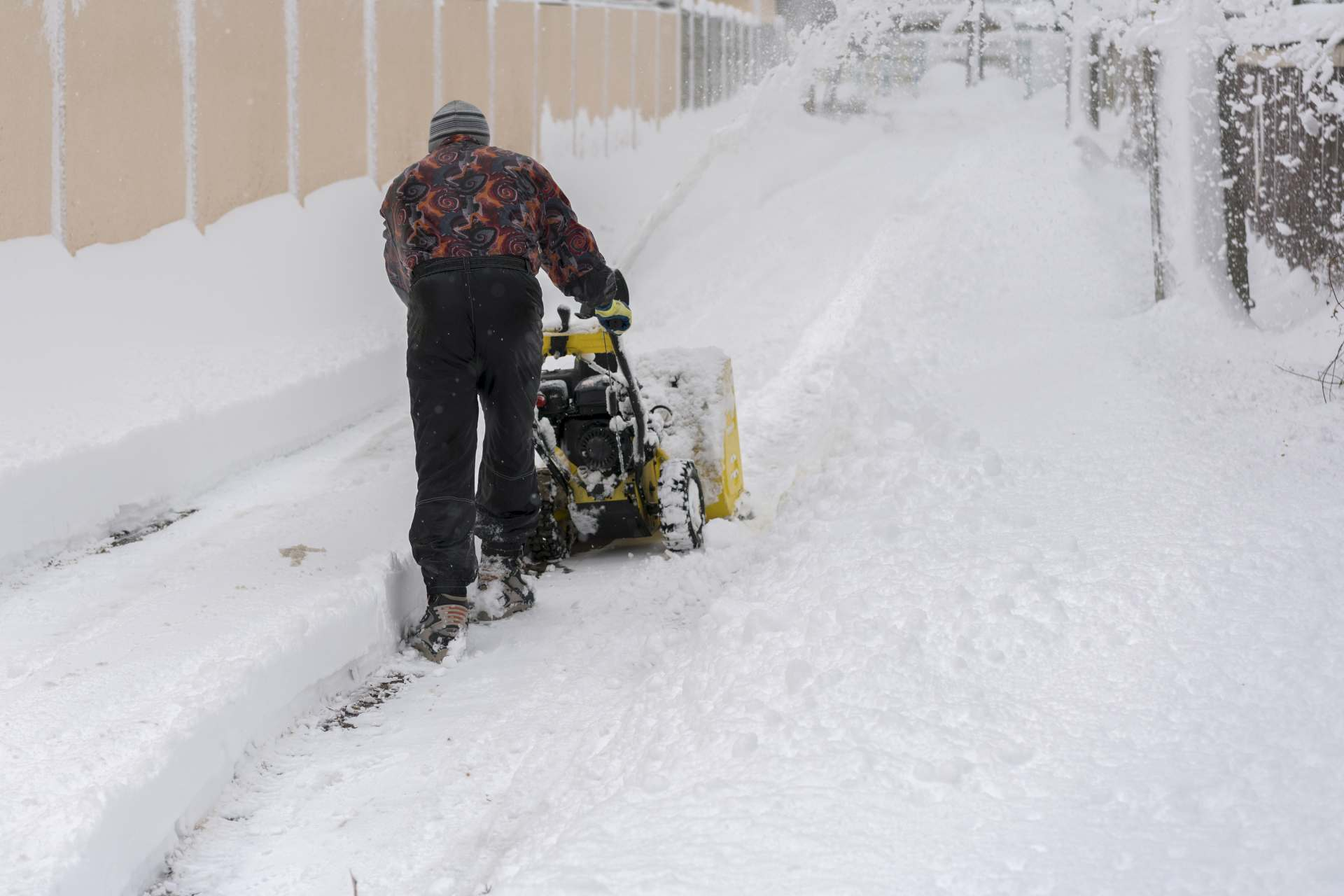 Man Operating Snow Blower to Remove Snow